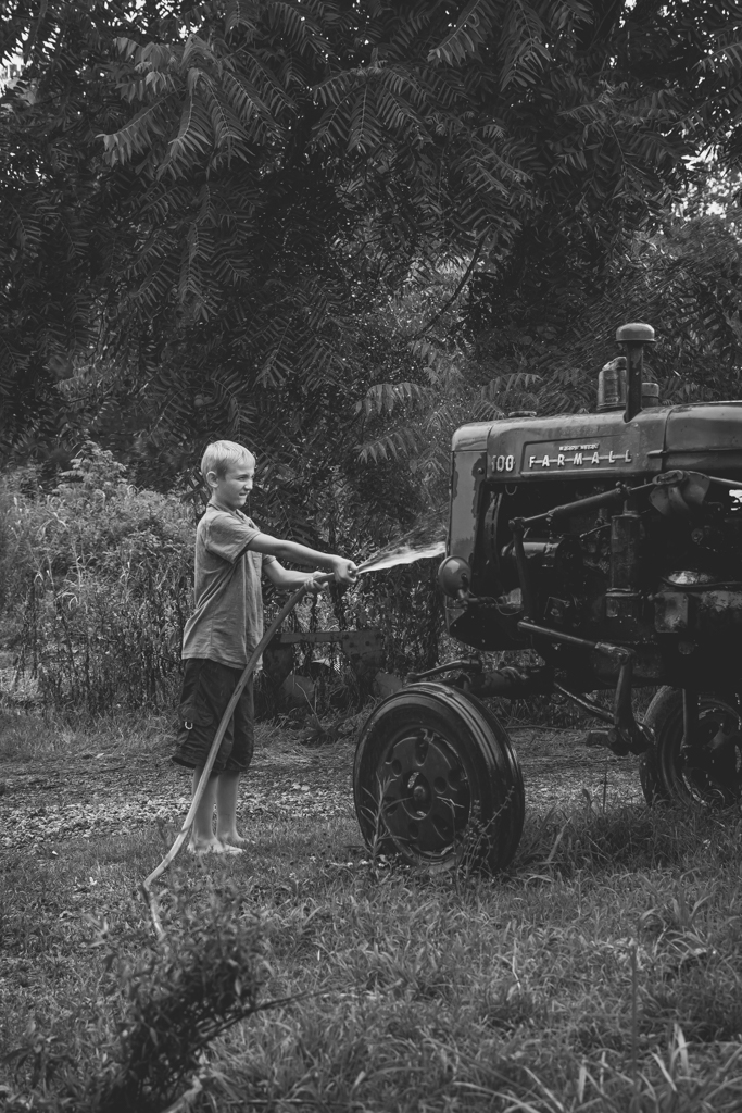Boy Washing a Farmall Tractor with a Water Hose